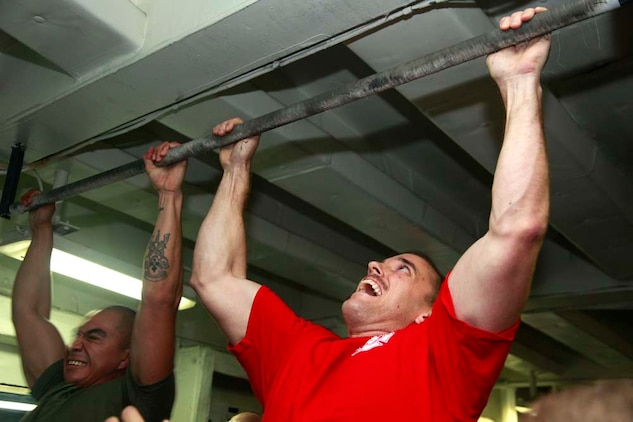 Corporal Cesar Carrillo, technical controller, Command Element, and Capt. Samuel C. Ksiazkiewicz, embarkation officer, Marine Medium Helicopter Squadron 364 (Rein.), both with 15th Marine Expeditionary unit, pull themselves up during the Campbell Cup Pull-Up Challenge in the gym of the USS Peleliu, Nov. 24. Marines and sailors of the 15th Marine Expeditionary Unit and Peleliu Amphibious Ready Group worked in teams of seven to see who could do the most pull-ups in ten minutes.  The 15th MEU is deployed as part of the Peleliu Amphibious Ready Group as a U.S. Central Command theater reserve force, providing support for maritime security operations and theater security cooperation efforts in the U.S. 5th Fleet area of responsibility. Carrillo, 24, is from Bell Gardens, Calif., and Ksiazkiewicz, 28, is from Jackson, Mich. (U.S. Marine Corps photo by Cpl. John Robbart III/Released)