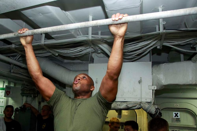 Sergeant Maj. John W. Scott, sergeant major, 15th Marine Expeditionary Unit, pulls himself up during the Campbell Cup Pull-Up Challenge in the gym of the USS Peleliu, Nov. 24. Marines and sailors of the 15th Marine Expeditionary Unit and Peleliu Amphibious Ready Group worked in teams of seven to see who could do the most pull-ups in ten minutes.  The 15th MEU is deployed as part of the Peleliu Amphibious Ready Group as a U.S. Central Command theater reserve force, providing support for maritime security operations and theater security cooperation efforts in the U.S. 5th Fleet area of responsibility. (U.S. Marine Corps photo by Cpl. John Robbart III/Released)
