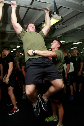 First Lt. James P. Rooney, platoon commander, Weapons Platoon, pulls himself up while 1st Lt. Murphy A. Bright, platoon commander, 3rd Platoon, both with Kilo Company, Battalion Landing Team 3/5, 15th Marine Expeditionary Unit, prevents him from swaying back and forth during the Campbell Cup Pull-Up Challenge in the gym of the USS Peleliu, Nov. 24. Marines and sailors of the 15th Marine Expeditionary Unit and Peleliu Amphibious Ready Group worked in teams of seven to see who could do the most pull-ups in ten minutes.  The 15th MEU is deployed as part of the Peleliu Amphibious Ready Group as a U.S. Central Command theater reserve force, providing support for maritime security operations and theater security cooperation efforts in the U.S. 5th Fleet area of responsibility. Rooney, 25, is form Long Island, N.Y., and Bright, 24, is from New York. (U.S. Marine Corps photo by Cpl. John Robbart III/Released)