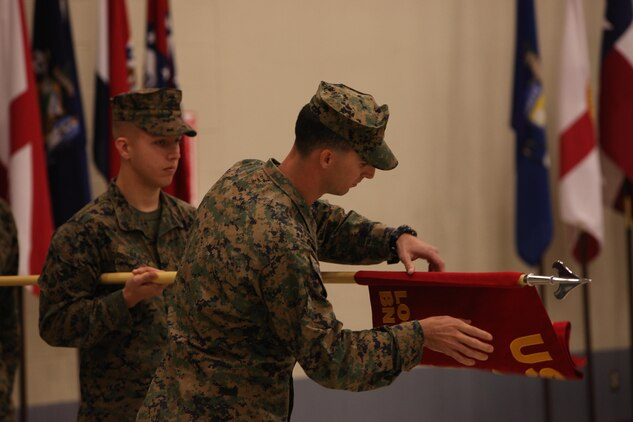 Captain Derek Ray, a logistics officer with the new Marine Special Operations Logistics Battalion, U.S. Marine Corps Forces, Special Operations Command, unfurls MSOLB's guidon during its activation ceremony aboard MARSOC headquarters, Camp Lejeune, NC, Nov. 15. Approximately 800 new Marines will arrive at MARSOC's new support components by 2016. (U.S. Marine Corps photo by Cpl. Kyle McNally/Released)