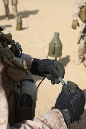 A Marine assigned to Engineer Detachment, Combat Logistics Battalion 15, 15th Marine Expeditionary Unit, prepares a fuse to use for a controlled detonation at a live-fire range near Camp Buehring, Kuwait, during a routine training exercise, Nov. 25. With the use of shape and cratering charges and composition C-4, the combat engineers were able to use the high explosives to demonstrate practical applications they could use in a combat environment. The 15th MEU is deployed as part of the Peleliu Amphibious Ready Group as a U.S. Central Command theater reserve force, providing support for maritime security operations and theater security cooperation efforts in the U.S. 5th Fleet area of responsibility. (U.S. Marine Corps photo by Cpl. Timothy R. Childers)