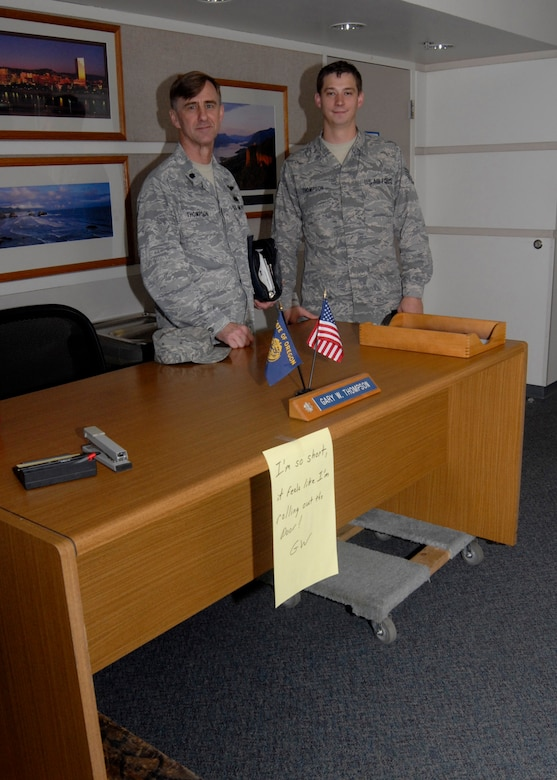 Oregon Air National Guard Lt. Col. Gary W. Thompson and his son Staff Sgt. Joshua Thompson stand behind Gary's desk as it has been put on weeks in the hallway to open his old office on his last day of active duty service, Oct. 31, 2012 at the Portland Air National Guard Base, Portland, Ore. (U.S. Air Force photo by Tech. Sgt. John Hughel, 142nd Fighter Wing Public Affairs / released)
