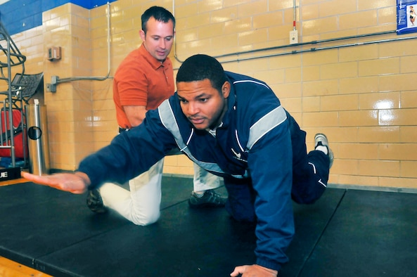 """Greg Reynolds, Robins Health and Wellness Center exercise physiologist helps Tech. Sgt. Bruce Thompson, 78th Logistics Readiness Squadron, do a core strengthening exercise called the """"birddog"""". (U. S. Air Force photo/Sue Sapp)"""