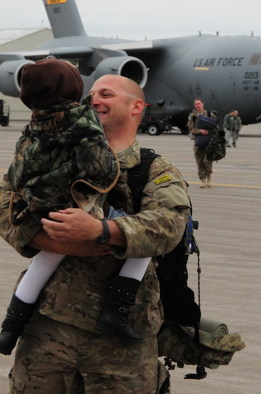 A 148th Fighter Wing member is greeted by his daughter after returning from Kandahar Airfield, Afghanistan, Oct. 22, 2012.  The 148th Fighter Wing, Minnesota Air National Guard, deployed approximately 300 airmen to Afghanistan in August, 2012 in support of Operation Enduring Freedom.  (National Guard photo by Tech. Sgt. Brett R. Ewald/ Released)