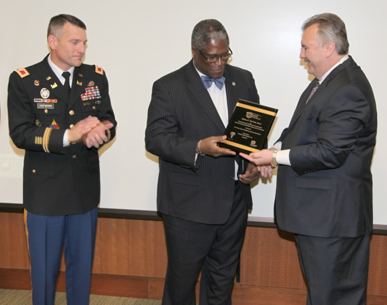 John L. Robinson, principal and owner of Strategic Value Solutions, Inc., presents Kansas City Mayor Sly James and Col. Anthony J. Hofmann, commander of the Kansas City District U.S. Army Corps of Engineers, with the Alphonse J. Dell'Isola Award for Outstanding Accomplishment in Construction on behalf of SAVE International during a presentation held Nov. 28, 2012. SVS, Inc. submitted the Blue River Channel Modification Project for the award. The redesigned project saved taxpayers approximately $35 million. U.S. Army Corps of Engineers photo by Rusty Thomas.