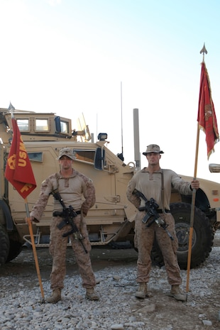 Sergeant William Whetzel, left, squad leader, Fox Company, 2nd Battalion, 7th Marines, Regimental Combat Team 7, holds the company's standard guidon while Sgt. Erik Frederiksen, squad leader, Fox Co., holds the guidon paying tribute to the Marines who came before them.