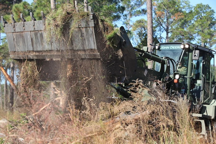 Lance Cpl. Lawrence Hulst, a Marine Wing Support Squadron 273 heavy equipment operator, clears brush on Paige Field, Nov. 19. The work of these Marines will improve the envirionment to better supprot the local wildlife and hunters.