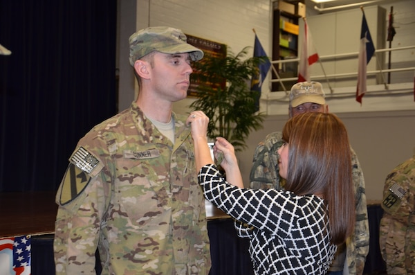 Sara Conner pins the rank of sergeant on her husband, Cpl. Christopher Conner Nov. 19 after the 440th Blood Support Detachment welcome home ceremony at Roadrunner Community Center on Joint  Base San Antonio-Fort Sam Houston. (Photo by Lori Newman, JBSA-Fort Sam Houston Public Affairs)