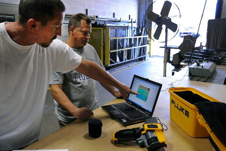 Bruce Zysk, left, and Darren Burton, a roofer and an electrician, respectively, with the 127th Civil Engineer Squadron at Selfridge Air National Guard Base, Mich., describe how they use a thermal imaging camera to develop energy saving techniques at the base. Zysk said by using the camera, he's able to prioritize roofing repairs to help Air National Guard maximize energy conservation efforts by tackling projects that represent the most heat loss fist. (Air National Guard photo by John S. Swanson)