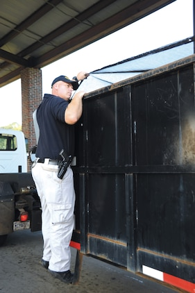 Lt. William Womble Jr., chief accident investigator, Marine Corps Police Department, inspects a garbage truck leaving Marine Corps Logistics Base Albany's commercial gate, Friday.