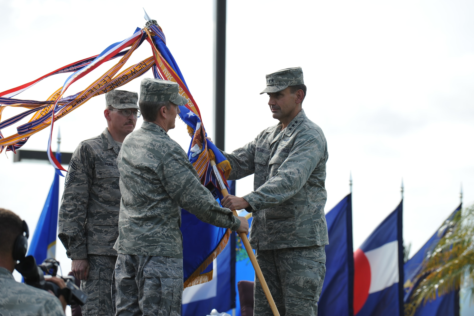 """Lt. Gen. Stanley T. Kresge, former 13th Air Force commander, passes the guidon to Gen. Herbert J. """"Hawk"""" Carlisle, Pacific Air Forces commander, to signify relinquishing his command during the 13th Air Force inactivation ceremony Sept. 28 at Joint Base Pearl Harbor-Hickam, Hawaii. (U.S. Air Force photo/Master Sgt. Victoria Meyer)"""