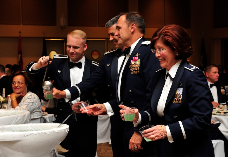 BUCKLEY AIR FORCE BASE, Colo. – Team Buckley members gather for a drink out of the grog bowl during a dining out Sept. 28, 2012, in the Leadership Development Center. Donning ones best Air Force attire, drinking from grog bowls and following rules of the mess are all time-honored traditions of the dining out. (U.S. Air Force photo by Airman 1st Class Darryl Bolden Jr.)
