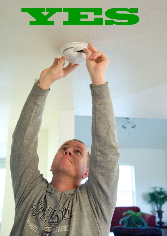 Staff Sgt. Robert Russell demonstrates how to properly check and change the battery in a smoke detector Oct. 1, 2012, at Dover Air Force Base, Del. The National Fire Protection Association urges residents to check batteries monthly and change them every six months. (U.S. Air Force photo illustration by Adrian R. Rowan)
