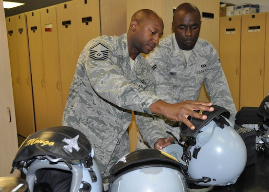 (Left) Master Sgt. Kevin Younger, 706th Fighter Squadron, explains to Airman 1st Class Keith Smith, 422nd Test and Evaluation Squadron Aircrew Flight Equipment Journeyman,  how to configure aircrew helmets with the Attenuation Custom Continuation Earpiece System. Younger is integrated into the 422nd TES as the Aircrew Flight Equipment flight chief. He was recently named the Air Force's Air Reserve Component Aircrew Flight Equipment Senior Noncommissioned Officer of 2011. (U.S. Air Force photo/Maj. Jessica Martin)