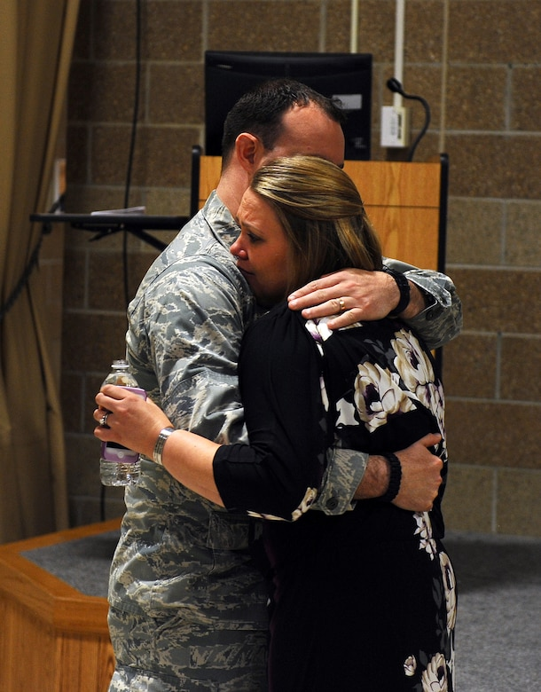 Kelly Nance leans into her husband for support following at Fallen Defenders and Master at Arms Dedication Ceremony held in the guard mount room of the 55th Security Forces Squadron headquarters at Offutt Air Force Base, Neb., Sept. 28.  Nance lost her brother, U.S. Navy Master at Arms 2nd class Sean Brazas, as he was serving in Panjaw'l, Afghanistan. (U.S. Air Force photo by Josh Plueger/Released)