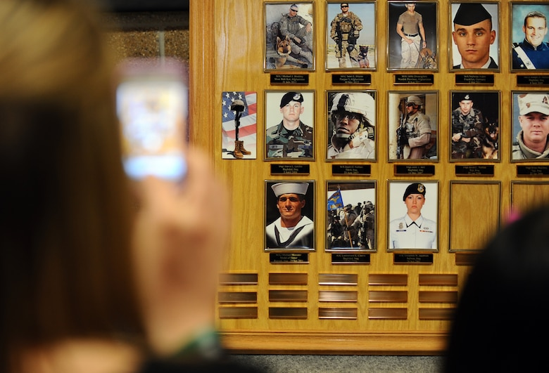 Kelly Nance takes a photo of the memorial in honor of the men and women who have fallen in combat while in the Security Forces career field at an annual Fallen Defenders and Master at Arms Dedication Ceremony held in the SFS guard mount room Offutt Air Force Base, Neb., Sept. 28.  Nance lost her brother, U.S. Navy Master at Arms 2nd class Sean Brazas, as he was serving in Panjaw'l, Afghanistan. (U.S. Air Force photo by Josh Plueger/Released)