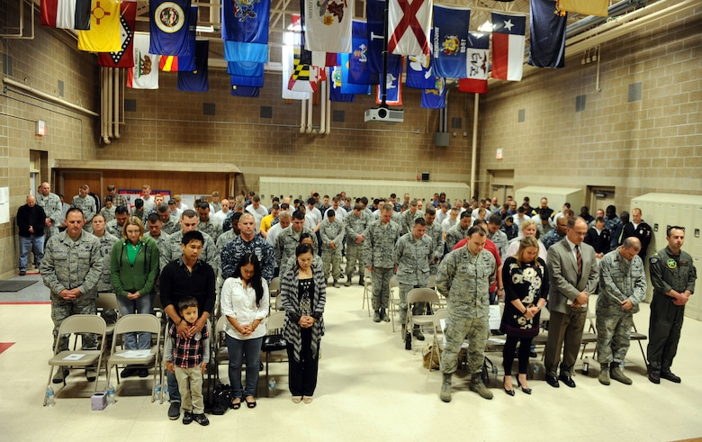 The men and women of the 55th Security Forces Squadron stand together in prayer at the conclusion of the annual Fallen Defenders and Master at Arms Dedication Ceremony held in the guard mount room of the 55th SFS building Offutt Air Force Base, Neb., Sept. 28.  Family members and coworkers were also in attendance to pay their respects to their fallen loved ones.  (U.S. Air Force photo by Josh Plueger/Released)