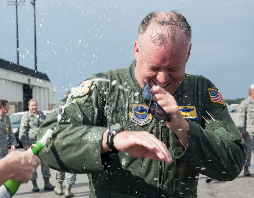 """Col. Erik Hansen is sprayed with sparkling grape juice by his wife Susan after completion of his final flight as the 437th Airlift Wing commander at Joint Base Charleston - Air Base, S.C., Oct. 2, 2012. The final or """"fini flight,"""" is an aviation tradition in which aircrew members are met by their unit comrades, family and friends and soaked with water. (U.S. Air Force photo/ Airman 1st Class Ashlee Galloway)"""