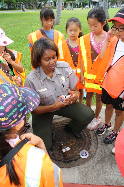 Angela Jones, head park ranger for the Corps' Regional Visitor Center, demonstrates how to install a storm drain marker for Girl Scout Brownie Troop 276 as part of National Public Lands Day, Sept. 29. The drain markers remind people to dump no waste since the water drains to the ocean. More than 60 volunteers scoured Fort DeRussy in Waikiki, picking up trash and installing storm drain markers as part of the national event. The Corps' Regional Visitor Center coordinated the event which was supported by Corps employees, Iolani School's Brownie Troop 276 and Punahou Junior ROTC cadets.