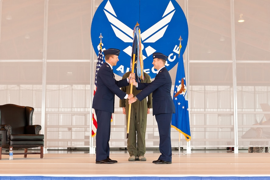 Colonel Kenneth Johnson, 49th Operations Group commander, hands the 9th Attack Squadron's guidon to Lt. Col. Jeffrey Patton, 9th Attack Squadron commander at Holloman Air Force Base, N.M., Sept. 28. The exchanging of the guidon symbolizes Patton assuming command of the newly-activated 9th Attack Squadron. The 9th Attack Squadron was activated to supplement the 29th Attack Squadron as a remotely piloted aircraft training squadron. (Courtesy photo)