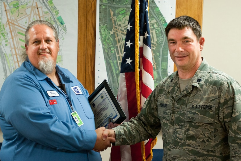 Kentucky Air National Guard Lt. Col. Phillip Howard, commander of the 123rd Civil Engineer Squadron, presents a certificate to Tony Roy, an airfield technician with the Louisville Regional Airport Authority in Louisville, Ky., on Sept. 21, 2012. Roy helped train Kentucky Air Guard civil engineers on the maintenance of commercial airfield lighting equipment, which enhanced their mission effectiveness during a 2011 deployment to Afghanistan. (Kentucky Air National Guard photo by Master Sgt. Phil Speck)