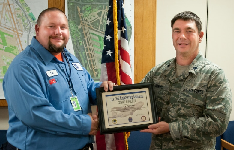 Kentucky Air National Guard Lt. Col. Phillip Howard, commander of the 123rd Civil Engineer Squadron, presents a certificate to Tom Hatfield, an airfield technician with the Louisville Regional Airport Authority in Louisville, Ky., on Sept. 21, 2012. Roy helped train Kentucky Air Guard civil engineers on the maintenance of commercial airfield lighting equipment, which enhanced their mission effectiveness during a 2011 deployment to Afghanistan. (Kentucky Air National Guard photo by Master Sgt. Phil Speck)