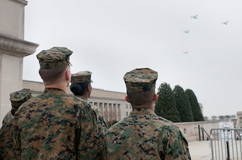ASCO Marines watch the overflight of a division of MV-22B Opsreys.  The ASCO Marines coordinated the flyover to provide funeral honors at nearby Arlington National Cemetery.