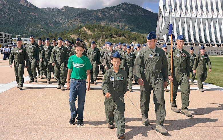 Wyatt Denton (center) and his brother Joe (left) march on the Terrazzo with Cadet Squardron 32 during Wyatt's Cadet for a Day experience Sept. 28, 2012. CS 32 was the sponsor squadron for Wyatt, a native of Parker, Colo. (U.S. Air Force photo/Sarah Chambers)