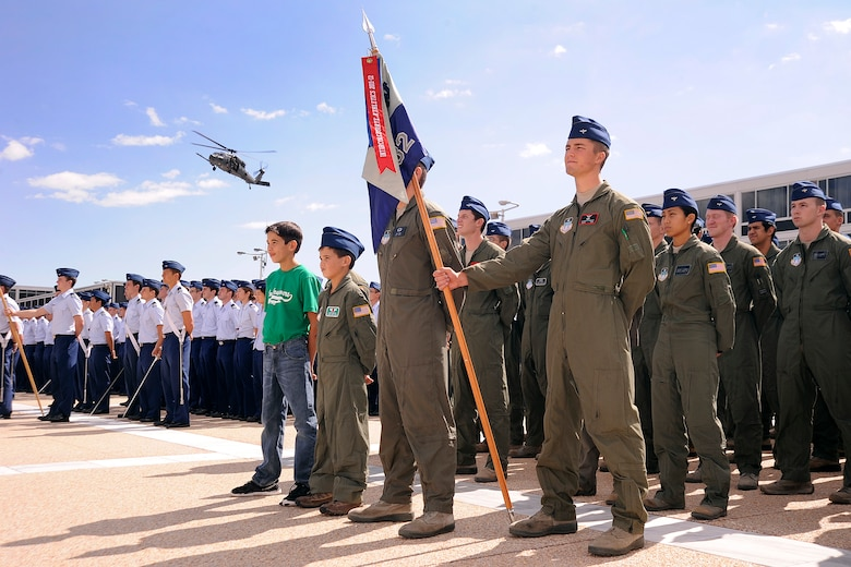 Joe and Wyatt Denton (center) stand at parade rest during a noon meal formation and HH-60 Pave Hawk flyover at the Air Force Academy Sept. 28, 2012. Wyatt was made a cadet for a day through the Academy's partnership with the Make-a-Wish Foundation. (U.S. Air Force photo/Sarah Chambers)