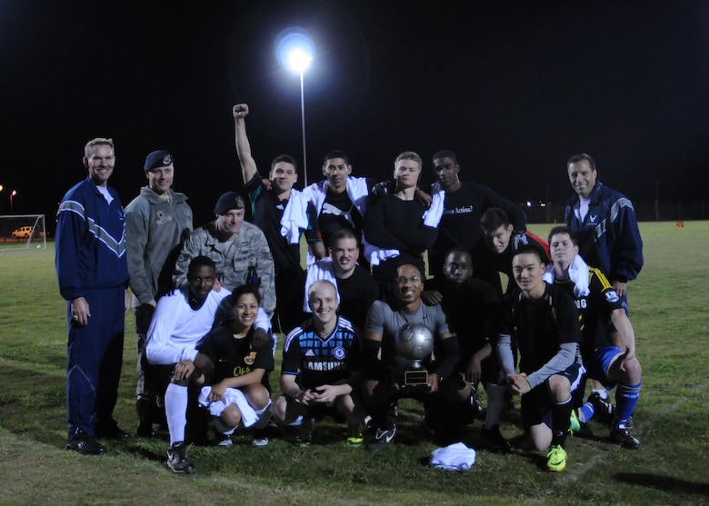 From right, Col. Christopher Kulas, 100th Air Refueling Wing commander, members of the 100th Security Forces Squadron's intramural soccer team, Lt. Col. David Harris, 100th SFS commander, and Chief Master Sgt. Christopher Powell, 100th ARW command chief, pose for a photo following the Team Mildenhall intramural soccer championship game Oct. 4, 2012, at RAF Mildenhall, England. 100th SFS played two games in one night against the 100th Civil Engineer Squadron; winning both to claim the trophy. (U.S. Air Force photo by Tech. Sgt. Neal X. Joiner/Released)