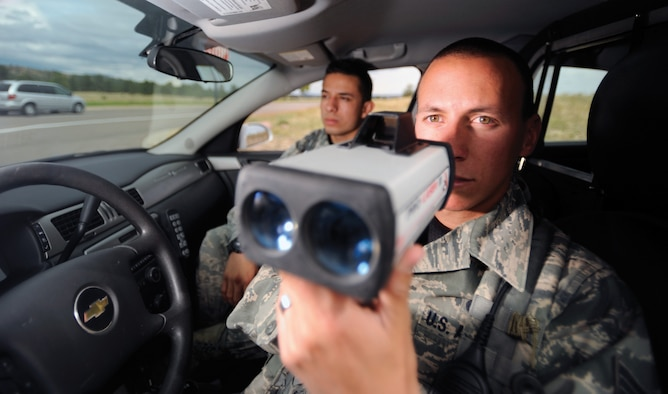 Senior Airman Brandon Aguirre (foreground) and Airman 1st Class Hans Castillo, patrollers with the 10th Security Forces Squadron, monitor drivers on South Gate Boulevard Sept. 26. Getting caught speeding on Academy grounds can be costly. (U.S. Air Force photo/Carol Lawrence)