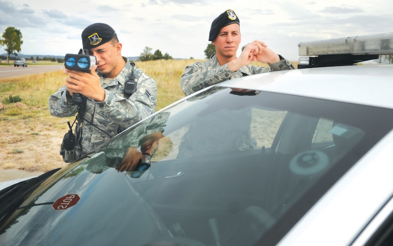 Airman 1st Class Hans Castillo and Senior Airman Brandon Aguirre, 10th Security Forces Squadron patrollers, use a radar gun to detect speeders on South Gate Boulevard Sept. 26. (U.S. Air Force photo/Carol Lawrence)