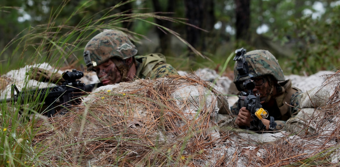 Lance Cpl. Christian Ponte (left), a team leader with Company B, 1st Battalion, 9th Marine Regiment, sights in with Pfc. Victor Levy (right), a basic rifleman, as they prepare for any enemy attacks on their position. Marines from 1/9 set up positions along a gridded area through which simulated enemy troops and vehicles would be trying to escape as part of their training Oct.1-4.