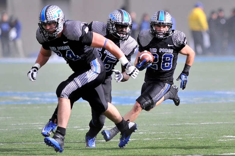 Falcons running back Cody Getz, right, follows his blockers during the Navy-Air Force football game at Falcon Stadium Oct. 6, 2012. Getz had 27 rushes for 206 yards, making him the first player in Air Force history and the second player in Mountain West Conference history with three 200-yard games in one season. (U.S. Air Force photo/Raymond McCoy)
