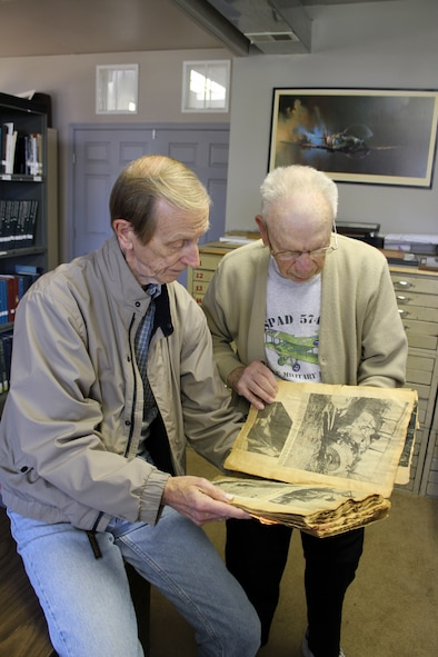 Dick Soules, left, and Frank Brown look at an old scrap book, possibly kept by a child in the 1930s, that is filled with newspaper clippings and other items that track the development of aviation. The scrapbook is a part of the collection of historical materials in the library of the Selfridge Military and Air Museum at Selfridge Air National Guard Base, Mich. The two men are among a group of a half dozen or so museum volunteers who are working on cataloging the various items that exist at the museum, such as the scrapbook. The two men were working at the museum on Oct. 9, 2012. (Air National Guard photo by TSgt. Dan Heaton)