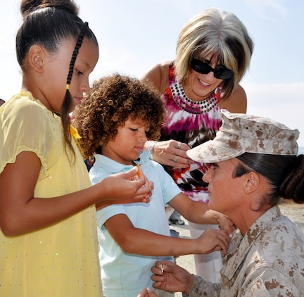 The children of Captain Kanella Hatchett, Marine Corps Tactical Systems Support Activity, pin the collar devices on the new Captain's uniform at her promotion ceremony while Hatchett's aunt observes.
