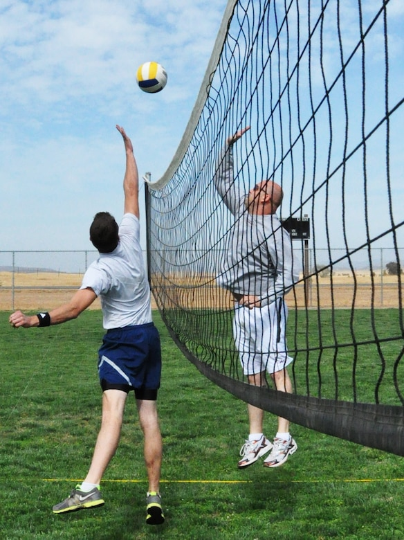 A 9th Civil Engineer Squadron team member (left) goes for a block against the 9th Maintenance Operations Squadron team during the volleyball portion of Beale Air Force Base's annual sports day Oct. 5. (U.S. Air Force photo by Tech. Sgt. Eric Petosky/Released)