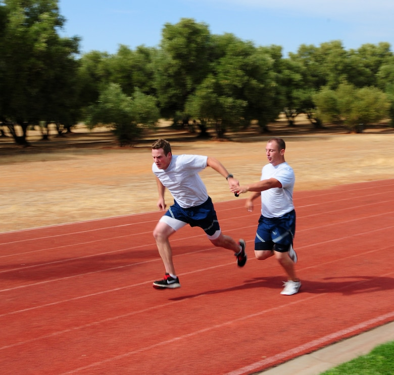 Members of Team Beale pass the baton during the base's annual sports day 400-meter relay at Beale Air Force Base Calif. Oct. 5, 2012. Each member of the four-man teams had to run 100 meters and complete a baton pass. If the baton dropped, that team was disqualified. (U.S. Air Force photo by Senior Airman Allen Pollard)