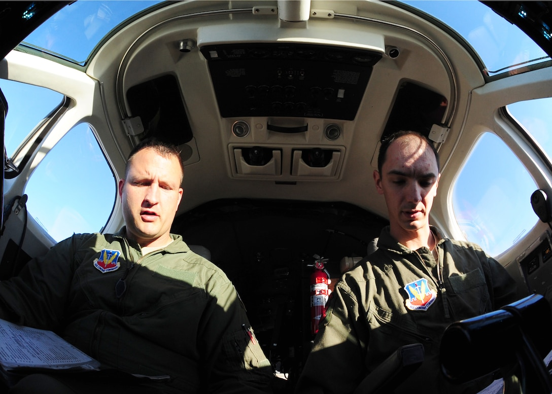 Two pilots complete a pre-flight checklist before their first flight ever in an Air Force MC-12W Liberty intelligence, surveillance, and reconnaissance aircraft at Beale Air Force Base Oct. 9, 2012. After training with the 489th Reconnaissance Squadron, the pilots will become part of the operations unit associated with the MC-12W, the 427th RS. (U.S. Air Force photo by Senior Airman Shawn Nickel/Released)