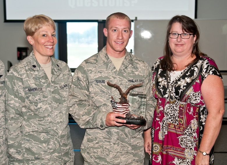 Senior Airman Nathan Rogers, an aerial porter for the Wisconsin Air Guard's 128th Logistics Readiness Squadron, receives the first-annual Chief Master Sergeant Tommy Downs Award for Excellence at the Logistics Readiness University in Savannah, Ga., on June 27, 2012. Also pictured are his commander, Lt. Col. Betsy Schoeller, and Janet Downs, wife to the late Chief Downs, a Kentucky Air Guardsman who was instrumental in founding the school. (U.S. Air Force photo by Master Sgt. Philip Speck)