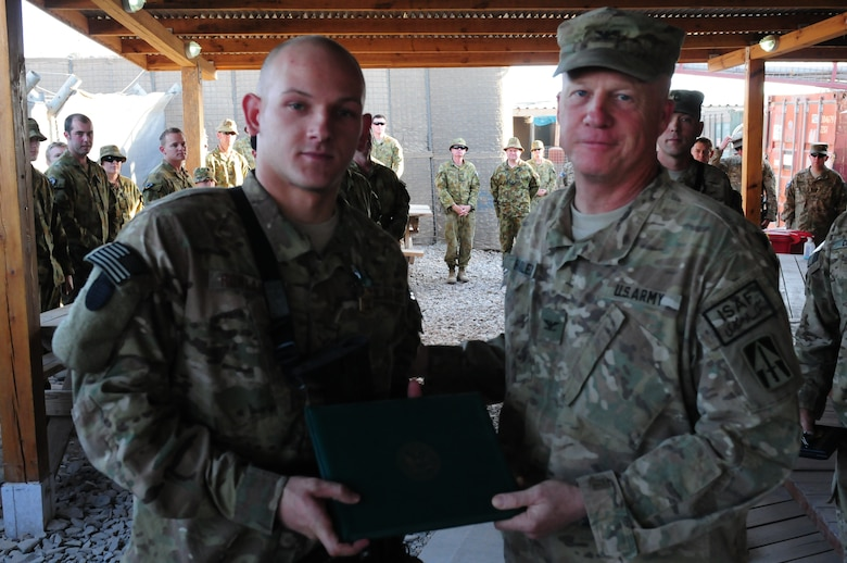 Col. Hadley, commander of the 76th IBCT, presents Airman 1st Class, 113th ASOS, the Army Commendation Medal.