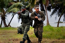 GAN, Republic of Maldives - Lance Cpl. Adam Haleem, a rifleman with Marine Deployment Unit 5 of the Maldivian National Defense Force, and Sgt. Sergio Zacarias, a squad leader with Company A, 1st Battalion, 4th Marine Regiment, run to their rally point during accountability training here Oct. 9 as part of Exercise Coconut Grove 2012. Coconut Grove is a bilateral training exercise conducted bi-annually between the U.S. Marine Corps and the MNDF.