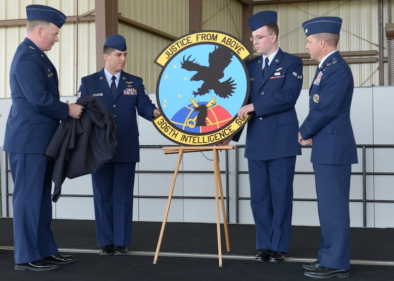 "BEALE AIR FORCE BASE, Calif. -- Col. Michael Stevenson (left), 361st Intelligence, Surveillance and Reconnaissance Group commander, admires the new squadron patch of the newly activated 306th Intelligence Squadron here, Oct. 5. Each part of the patch, which says ""Justice From Above,"" signifies a function of the squadron. (U.S. Air Force photo by John Schwab)"
