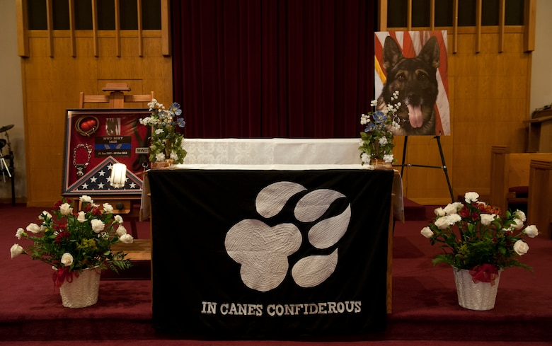A memorial sits on display in honor of military working dog Roky during a service at the base chapel at Holloman Air Force Base, N.M., Oct. 11. Roky, a 5-year-old German Shepherd, died after a demonstration at Holloman AFB Oct. 2. Roky served as a military working dog at Holloman AFB and in deployed locations. While deployed, Roky found more than 10,000 grams of illegal narcotics, conducted a thousand random anti-terrorism measures, and performed 400 hours of foot patrol. (U.S. Air Force photo by Airman Leah Ferrante/Released)