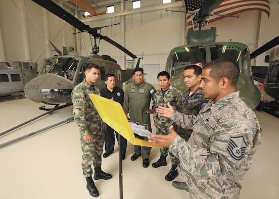 Master Sgt. Guadalupe Arredondo, instructor-supervisor, 318th Training Squadron, right, discusses helicopter towing procedures with, from left to right, students E-1 Powell Murillo, Colombia, O-2 Julio Hortiales, Mexico, E-6 Fernando Toscano, Argentina, E-1 Yamid Camacho, Colombia, and guest instructor PNGI E-8 Mario Ordoñez, Honduras, prior to moving an Army Huey UH-1H helicopter outside the Inter-American Air Forces Academy's Airfield Training Complex High Bay Oct. 1. The UH-1H will be used to train students from Latin American partner nations. (U.S. Air Force photo/Robbin Cresswell)
