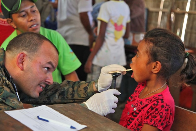 Lieutenant Com. Delbert Clark, senior medical provider, Combat Logistics Battalion 15, 15th Marine Expeditionary Unit, checks a child's mouth for illness or injury in a Timor-Leste village, Oct. 11, during Exercise Crocodilo 2012, the first exercise the 15th MEU and Peleliu Amphibious Ready Group has conducted during its Western Pacific deployment. During the exercise a total of 10 sights were visited in which corpsmen from the MEU  gave health screenings and vaccinations, made surgery referrals to a local hospital, provided dental care to include tooth removal, gave optometry screenings, prescribed and provided eyeglasses and issued medication and vitamins for minor illnesses or injuries.
