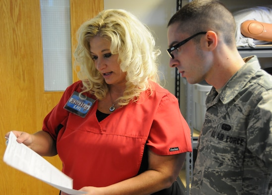 Shelley Fleetwood, Logistics Health team lead, explains to Senior Airman Chris Winship, 267th Combat Communications Squadron cyber transport technician, how to fill out his medical paperwork prior to his examination at the 102nd Medical Group building on Otis Air National Guard Base, Mass. Oct. 13-14. The Logistics Health dental team treated approximately 120 servicemembers throughout the weekend. (Air National Guard photo by Senior Airman Patrick McKenna/Released)