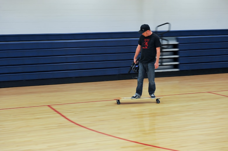 BUCKLEY AIR FORCE BASE, Colo. - Aaron McKeulich, creative director of Knights of the Air, films during an on-base long board demonstration Oct. 12, 2012, at the Buckley Fitness Center.  KOTA is a local longboard company started by veteran military aviators. (U.S. Air Force photo by Airman 1st Class Phillip Houk)