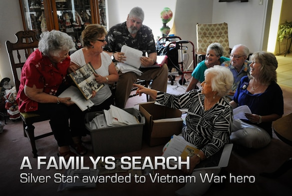 Relatives laugh as Debra Morris, second from left, a niece of the late U.S. Air Force Master Sgt. James Calfee, shows a photo of her uncle from his high school yearbook in Houston, Texas, Aug. 22, 2012. Calfee, who was posthumously awarded the Silver Star Medal, was killed in action in Laos in 1968. (U.S. Air Force photo/Val Gempis)