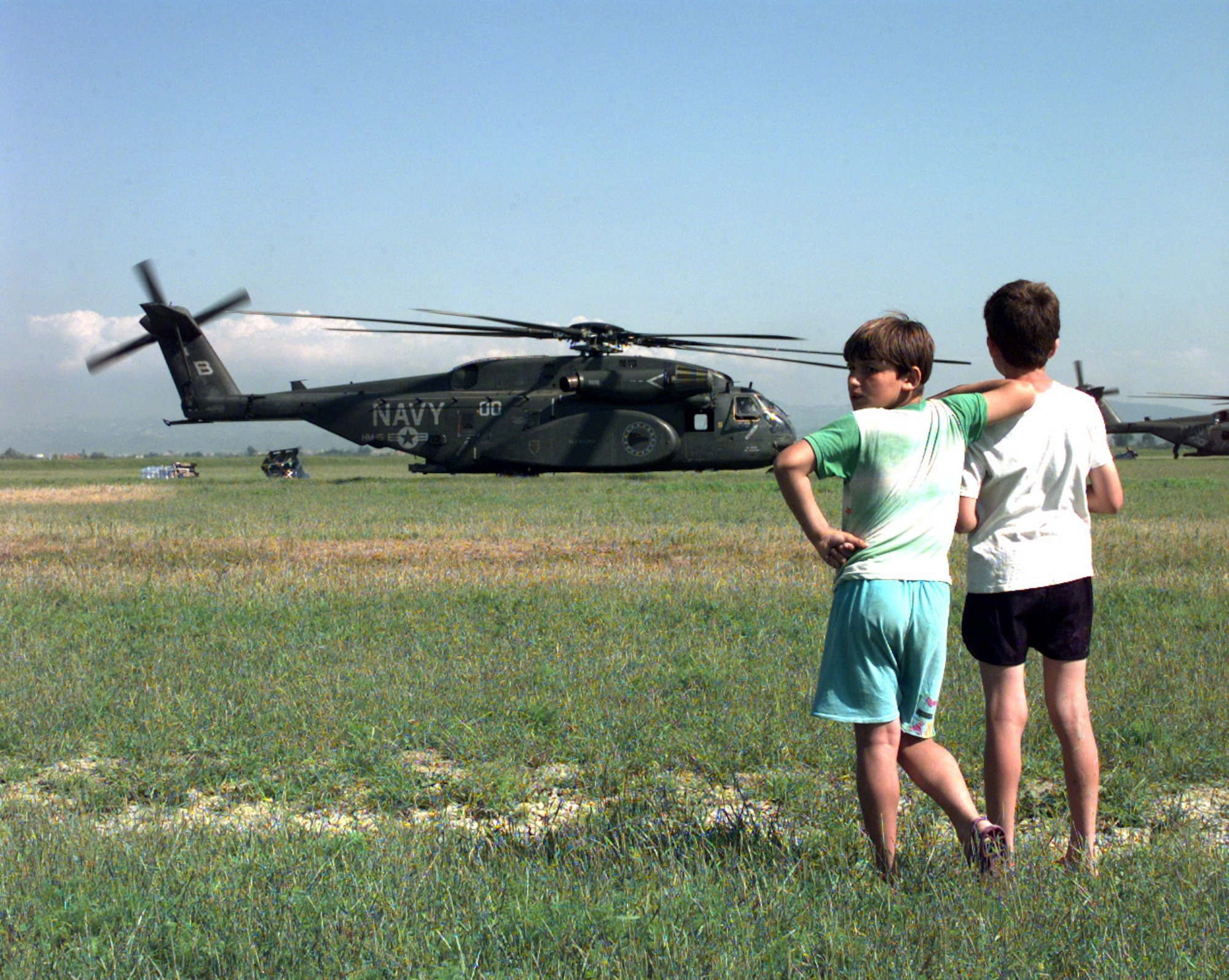 Two refugee children watch as relief supplies are unloaded from U.S. Navy MH-53E Sea Dragon helicopters at Camp Hope near Fier, Albania, on May 13, 1999, during Operation Sustain Hope. Sustain Hope brought in food, water, medicine, relief supplies, and established camps for refugees fleeing from the Former Republic of Yugoslavia. (U.S. Air Force photo by Senior Airman Michelle Leonard)